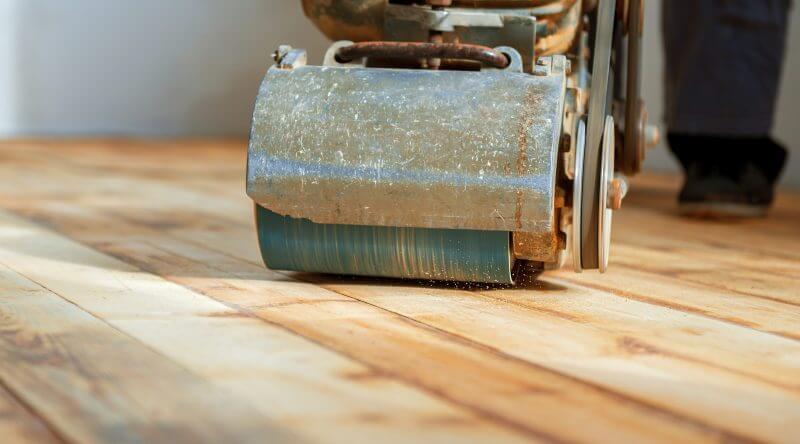 man sanding hardwood floor