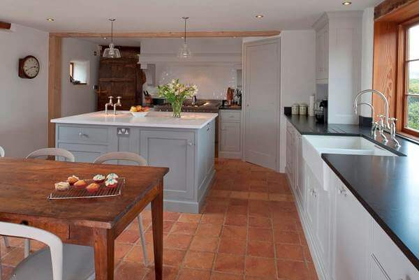 Traditional square terracotta flagstones work perfectly with this modern  farmhouse kitchen.