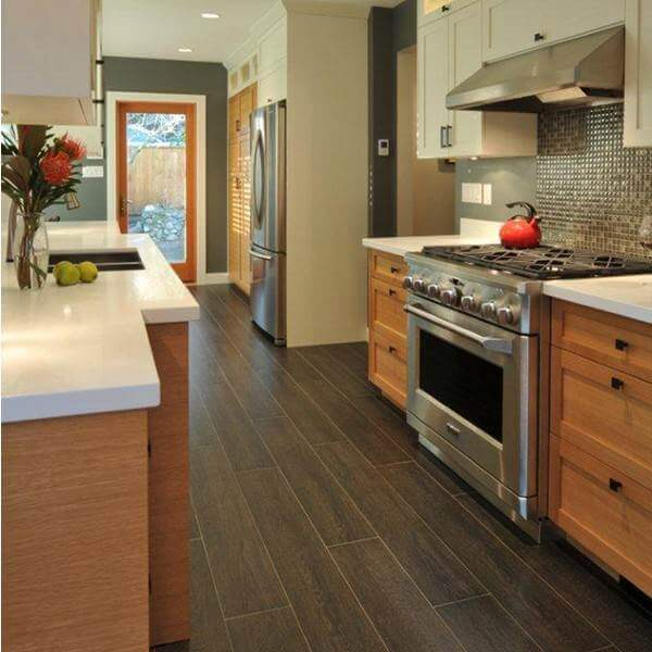 A traditional looking wood look tile is both practical and pretty in this galley kitchen