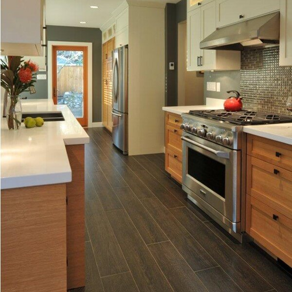 A traditional looking wood look tile is both practical and pretty in this galley kitchen.