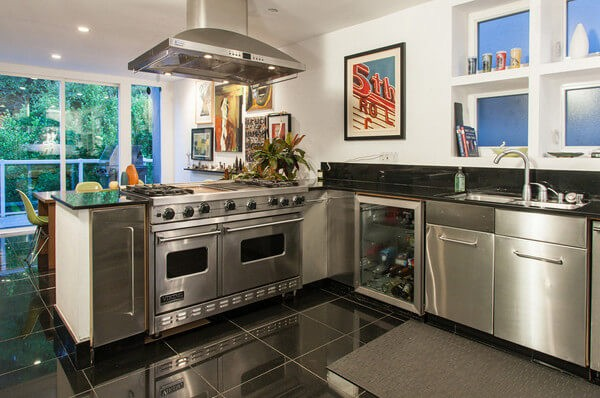 Mirror-like high gloss black tiles add extra glamor to this gorgeous kitchen.