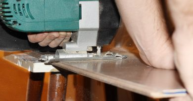 man cutting laminate flooring with saw