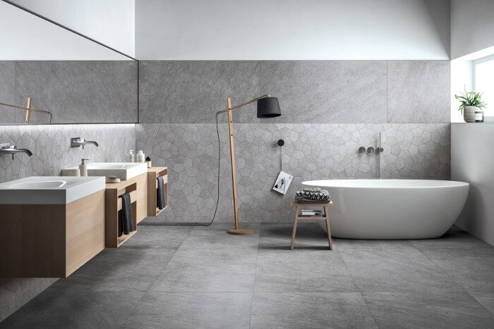 Soft matt stone look floor tiles pair with geometric wall tiles, both from Refin's Grecale collection, to create this superb minimalist bathroom.